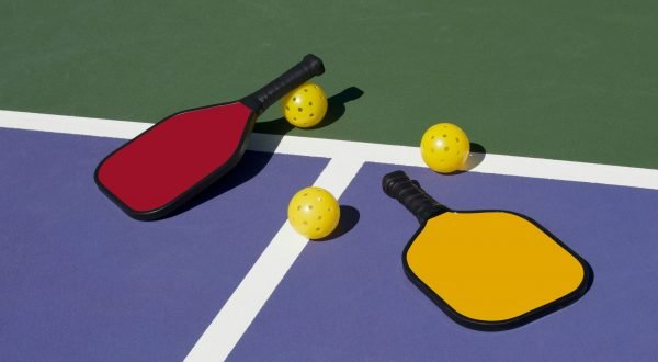 Pickleball paddles & pickleball balls on a pickleball court