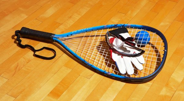 Racquetball racket, racquetball ball, racquetball glove, racquetball protective eyewear on a racquetball court