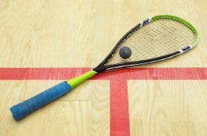 squash racket on a squash court with a squash ball